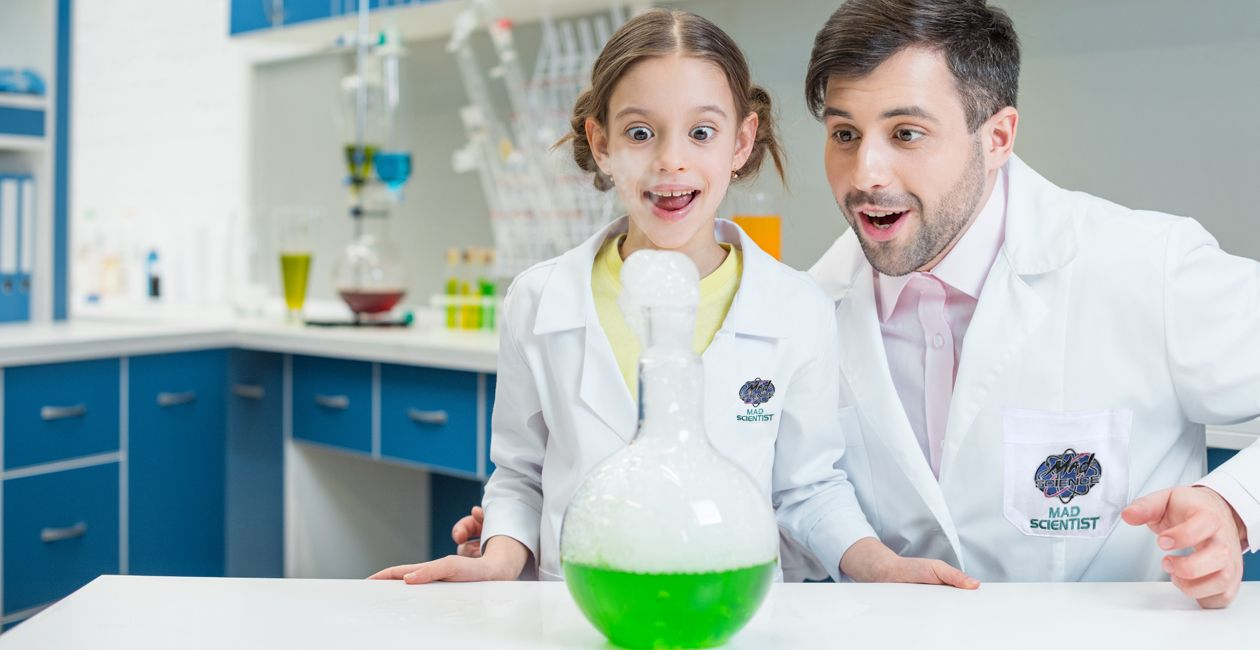 Scientist and little girl in lab looking at a flask with a green liquid inside.